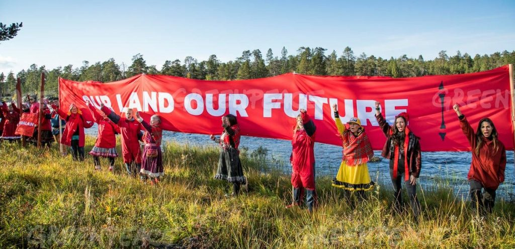 "Sámi activists with a banner saying ""Our land our future""."